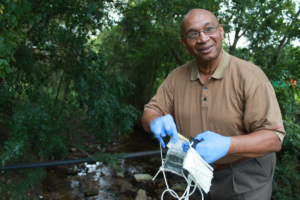 A trained volunteer collects water samples from a public bridge. Photo: CRK
